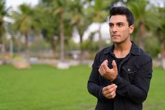 Young handsome Hispanic man relaxing in the park outdoors. Portrait of young handsome Hispanic man in the park outdoors royalty free stock photography