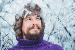 Portrait of a young handsome man with a beard. A person close up of a bearded man. Bearded man froze in the winter woods Royalty Free Stock Images