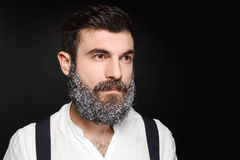 Portrait of young handsome man with beard in snow over black background. Stock Photo