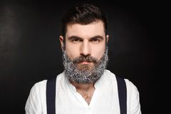 Portrait of young handsome man with beard in snow over black background. Stock Image