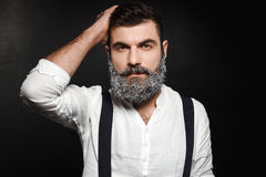 Portrait of young handsome man with beard in snow over black background. Stock Photography
