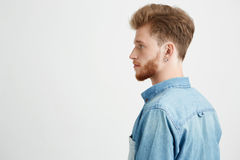 Portrait of young handsome man with beard wearing jean shirt standing in profile over white background. Copy space Stock Photos