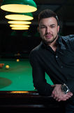 Portrait of young handsome man in billiard club. Royalty Free Stock Photo
