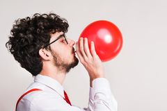 Portrait of a young man with balloon in a studio. stock photos