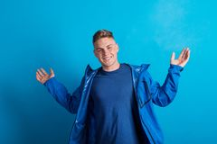 Portrait of a young man with blue anorak in a studio, standing against blue background. Portrait of a young handsome man with blue anorak in a studio, standing stock images