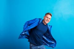 Portrait of a young man with blue anorak in a studio, standing against blue background. Portrait of a young handsome man with blue anorak in a studio, standing royalty free stock photography
