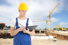 Portrait of young handsome man in  builder uniform with clipboar Stock Photo