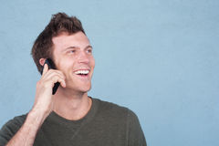 Portrait of a young handsome man on the cell phone. Outside  on a blue background Stock Photos