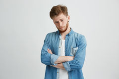 Portrait of young handsome man with crossed arms raising up brow looking at camera over white background. Royalty Free Stock Image