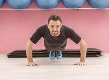 Portrait of a Young Man Doing Pushups. Portrait of a young handsome man doing pushups in a gym Stock Images