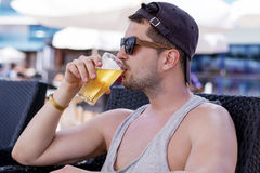 Portrait of young handsome man drinking cold refreshing beer. Outdoor Royalty Free Stock Image