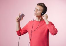 Portrait of a young handsome man with headphones listening a music with a smartphone stock photo