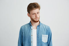 Portrait of young handsome man in jean shirt raising up brow looking at camera over white background. Royalty Free Stock Image