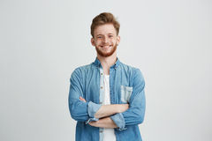 Portrait of young handsome man in jean shirt smiling looking at camera with crossed arms over white background. Copy space Royalty Free Stock Photo