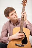 Portrait of young handsome man playing on acoustic guitar Stock Images