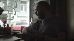 Portrait of young handsome man sitting in cafe near the window and using the smartphone, surfing the Internet. stock video