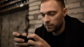 Portrait of young handsome man sitting in the city centre in the evening and using the smartphone with touchscreen. Attractive male spending time in downtown stock footage
