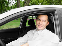 Portrait of young handsome man smiling in his own car Royalty Free Stock Photography