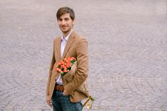 Portrait of young handsome man smiling holding a bunch of roses. Portrait of young man holding a bunch of roses under arm on a city gray pavage background Royalty Free Stock Photography