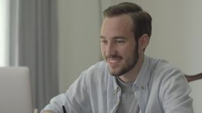 Portrait of a young handsome man smiling and nodding sitting in front of his computer in the office. The office worker stock video footage