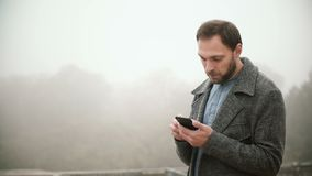 Portrait of young handsome man standing in foggy park in early morning. Bearded male using smartphone with touchscreen. Attractive man chatting in social stock video footage