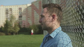 Portrait of young handsome man standing near a metal fence in a city background. Young attractive man standing near a metal fence in a city background, outdoor stock video