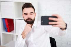 Portrait of handsome man taking selfie photo with smartphone royalty free stock photography