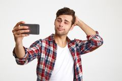 Portrait of a young handsome man taking a selfie. While standing isolated over white background royalty free stock photo