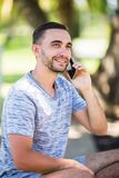 Portrait of young handsome young man talking on the cell phone royalty free stock photography