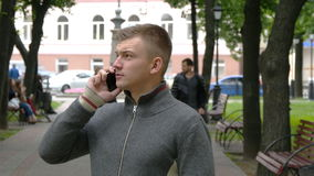 Portrait of a young handsome man talking on cell phone on the city park Royalty Free Stock Image