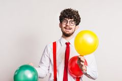 Portrait of a young man with balloons in a studio. royalty free stock images