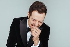 Young handsome man in a tuxedo, laughing, holding hand near fac. Portrait of a young handsome man in a tuxedo, laughing, holding hand near face, against pl royalty free stock photo