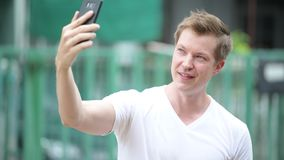 Young handsome man using mobile phone in the streets outdoors. Portrait of young handsome man using mobile phone in the streets outdoors stock footage