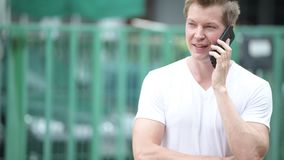 Young handsome man using mobile phone in the streets outdoors. Portrait of young handsome man using mobile phone in the streets outdoors stock video