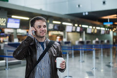 Portrait of young handsome man walking in modern airport terminal, talking smart phone, travelling with bag and coffee Royalty Free Stock Photos