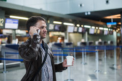 Portrait of young handsome man walking in modern airport terminal, talking smart phone, travelling with bag and coffee Stock Photos