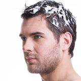 Portrait young handsome man washing hair. Royalty Free Stock Images