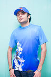 Portrait of Young Handsome Man Wearing blue V neck T shirt, black pants, flat cap, standing by painted wall. Royalty Free Stock Photography