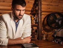 Portrait of young handsome man in white suit against wooden background. Photo stock photos