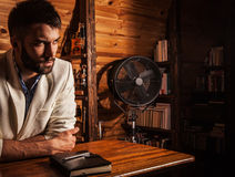 Portrait of young handsome man in white suit near home bar. Photo stock photos