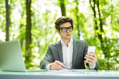 Portrait of young handsome manager working at laptop at office table and talk at phone with costumer and make notice in green fore. Portrait of young handsome stock image