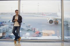 Portrait of young handsome person wearing casual style clothes standing near window in modern airport terminal. Traveler. Making call using smartphone Stock Image