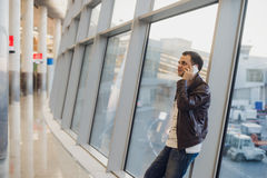 Portrait of young handsome person wearing casual style clothes standing near window in modern airport terminal. Traveler. Making call using smartphone Royalty Free Stock Images