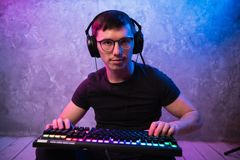 Portrait of the young handsome pro gamer sitting on the floor with keyboard in neon colored room royalty free stock photography
