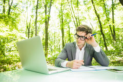 Portrait of young handsome sad business man in suit working at laptop at office table in green forest park. Business concept. Portrait of young handsome sad stock image