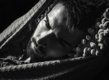 Portrait of young handsome serious man in a hammock. Black-white close-up photo stock image