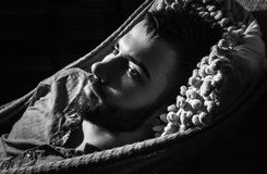 Portrait of young handsome serious man in a hammock. Black-white close-up photo royalty free stock images