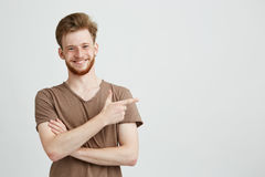 Portrait of young handsome sincere man with beard smiling looking at camera pointing finger in side over white Stock Photos