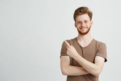 Portrait of young handsome sincere man with beard smiling looking at camera pointing finger in side over white Stock Photo