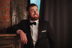 Portrait of young handsome smiling ginger man with beard in the dark room Royalty Free Stock Photography